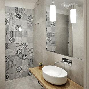 Ispirazione per una stanza da bagno con doccia minimal con nessun'anta, ante in legno scuro, doccia aperta, piastrelle grigie, piastrelle in gres porcellanato, lavabo a bacinella e top in legno