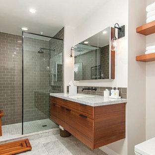 Idéer för små 60 tals en-suite badrum, med släta luckor, skåp i mellenmörkt trä, en öppen dusch, en toalettstol med separat cisternkåpa, beige kakel, glaskakel, vita väggar, marmorgolv, ett undermonterad handfat, marmorbänkskiva, vitt golv och med dusch som är öppen