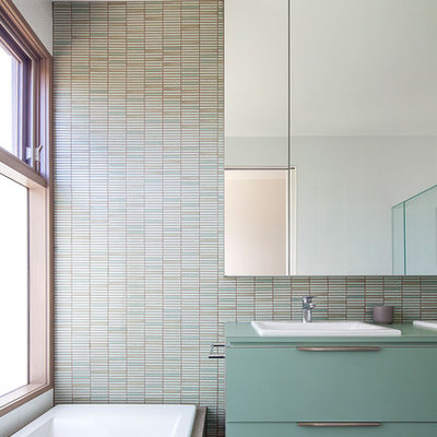 Trendy master black floor drop-in bathtub photo in Melbourne with flat-panel cabinets, green cabinets, multicolored walls and a drop-in sink
