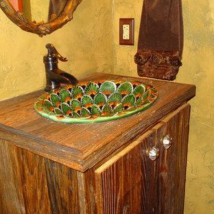 シャーロットの小さいラスティックスタイルのおしゃれなバスルーム (浴槽なし) (オーバーカウンターシンク、家具調キャビネット、濃色木目調キャビネット、木製洗面台、アルコーブ型シャワー、分離型トイレ、マルチカラーのタイル、セラミックタイル、黄色い壁、無垢フローリング) の写真