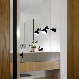 Photo of a contemporary bathroom in Sydney with flat-panel cabinets, light wood cabinets, white walls, an undermount sink, black floor and grey benchtops.