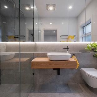 Design ideas for a scandinavian 3/4 bathroom in Newcastle - Maitland with an alcove shower, a wall-mount toilet, gray tile, grey walls, a vessel sink, wood benchtops, grey floor and brown benchtops.