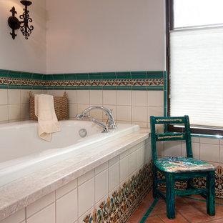 Inredning av ett medelhavsstil badrum, med ett platsbyggt badkar, flerfärgad kakel, vita väggar och klinkergolv i terrakotta