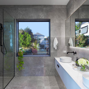 Photo of a contemporary bathroom in Brisbane with gray tile, stone tile, grey walls, concrete floors, grey floor, a double vanity, flat-panel cabinets, white cabinets, a curbless shower, a vessel sink, white benchtops and a floating vanity.