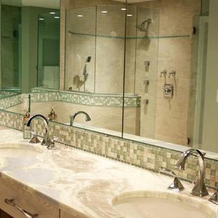 На фото: главная ванная комната среднего размера в морском стиле с фасадами в стиле шейкер, фасадами цвета дерева среднего тона, угловой ванной, угловым душем, унитазом-моноблоком, бежевой плиткой, керамической плиткой, бежевыми стенами, врезной раковиной, столешницей из кварцита, душем с распашными дверями, полом из керамической плитки и бежевым полом с