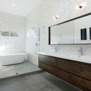 Создайте стильный интерьер: главная ванная комната в современном стиле с плоскими фасадами, темными деревянными фасадами, отдельно стоящей ванной, душем в нише, белой плиткой, белыми стенами, бетонным полом, монолитной раковиной, серым полом, открытым душем и белой столешницей - последний тренд