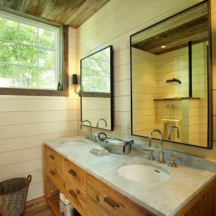 Modelo de cuarto de baño campestre con lavabo bajoencimera, armarios tipo mueble y puertas de armario de madera oscura