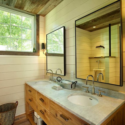 Farmhouse bathroom photo in New York with an undermount sink, furniture-like cabinets and medium tone wood cabinets