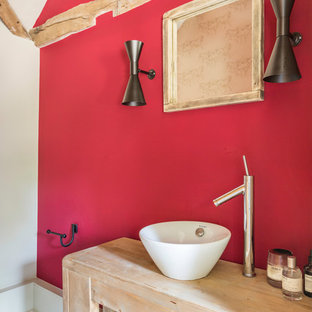 Rural bathroom with light wood cabinets, red walls, a vessel sink and grey floors.