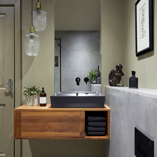This is an example of a world-inspired bathroom in London with flat-panel cabinets, medium wood cabinets, a one-piece toilet, grey tiles, green walls, a vessel sink, wooden worktops, grey floors and brown worktops.