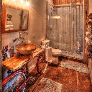 他の地域の中サイズのラスティックスタイルのおしゃれなバスルーム (浴槽なし) (オープンシェルフ、ベージュのキャビネット、アルコーブ型シャワー、分離型トイレ、グレーのタイル、メタルタイル、ベージュの壁、コンクリートの床、ベッセル式洗面器、木製洗面台、茶色い床、開き戸のシャワー、ベージュのカウンター) の写真