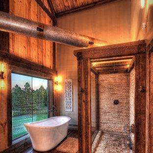 他の地域の広いラスティックスタイルのおしゃれなマスターバスルーム (家具調キャビネット、白いキャビネット、置き型浴槽、オープン型シャワー、分離型トイレ、ベージュのタイル、石タイル、ベージュの壁、無垢フローリング、ベッセル式洗面器、木製洗面台、茶色い床、オープンシャワー、ベージュのカウンター) の写真