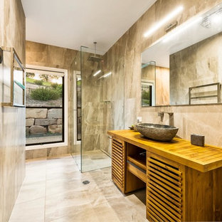 Inspiration for a mid-sized country bathroom in Other with louvered cabinets, brown cabinets, an alcove shower, marble, a vessel sink, wood benchtops, beige walls, marble floors, beige floor, a hinged shower door and beige benchtops.