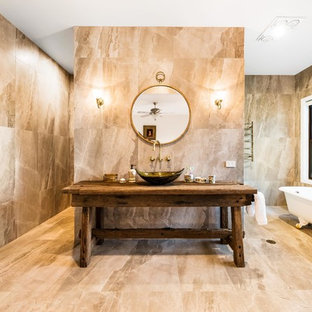 Inspiration for a country 3/4 bathroom in Other with a claw-foot tub, beige tile, beige walls, wood benchtops, beige floor and a vessel sink.