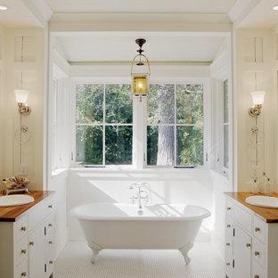 Immagine di una stanza da bagno in montagna con vasca con piedi a zampa di leone, top in legno e top marrone