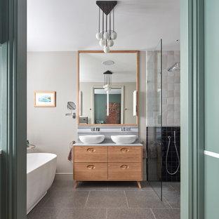На фото: большая главная ванная комната в современном стиле с фасадами островного типа, светлыми деревянными фасадами, отдельно стоящей ванной, открытым душем, черно-белой плиткой, цементной плиткой, полом из терраццо, настольной раковиной, мраморной столешницей, открытым душем, разноцветной столешницей, серыми стенами и серым полом с