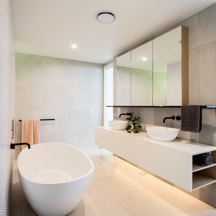 Contemporary bathroom in Sunshine Coast with a freestanding tub, gray tile, a vessel sink, beige floor, white benchtops, a double vanity and a floating vanity.