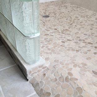Ejemplo de cuarto de baño principal, tradicional renovado, grande, con armarios con paneles empotrados, puertas de armario de madera en tonos medios, encimera de acrílico, ducha abierta, suelo de baldosas tipo guijarro, paredes beige y suelo de baldosas de cerámica