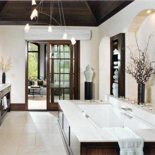 Idee per una stanza da bagno padronale chic con nessun'anta, ante in legno bruno, vasca sottopiano, pareti beige, lavabo sottopiano, pavimento in pietra calcarea e pavimento beige
