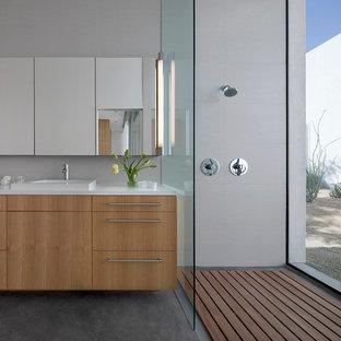 Foto di una piccola stanza da bagno padronale design con ante lisce, ante in legno chiaro, doccia aperta, piastrelle bianche, piastrelle in gres porcellanato, pareti bianche, pavimento in cemento, top in superficie solida, lavabo da incasso e doccia aperta