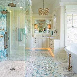 Modelo de cuarto de baño principal, marinero, con armarios con paneles empotrados, puertas de armario beige, bañera exenta, ducha a ras de suelo, baldosas y/o azulejos azules, baldosas y/o azulejos multicolor, baldosas y/o azulejos blancos, paredes beige, suelo multicolor y encimeras blancas