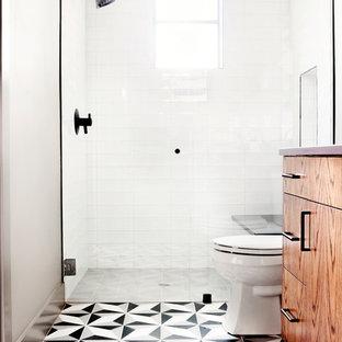 Klassisk inredning av ett litet badrum med dusch, med släta luckor, skåp i mellenmörkt trä, en dusch i en alkov, en toalettstol med separat cisternkåpa, vit kakel, porslinskakel, vita väggar, cementgolv, ett undermonterad handfat, bänkskiva i akrylsten, flerfärgat golv och dusch med gångjärnsdörr