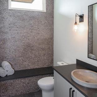 Foto de cuarto de baño actual, pequeño, con armarios estilo shaker, puertas de armario grises, baldosas y/o azulejos grises, suelo de baldosas tipo guijarro, paredes blancas, suelo de baldosas de porcelana, lavabo sobreencimera, encimera de cuarzo compacto, suelo gris y encimeras negras