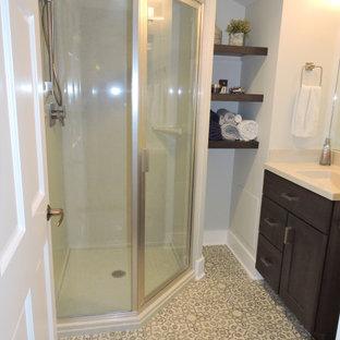 Modelo de cuarto de baño contemporáneo, pequeño, con armarios con paneles empotrados, puertas de armario de madera en tonos medios, ducha esquinera, paredes blancas, suelo vinílico, lavabo integrado, ducha con puerta con bisagras, encimeras beige, encimera de ónix y suelo multicolor