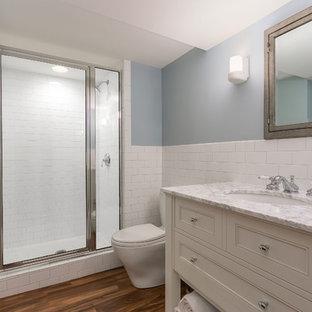 Mittelgroßes Klassisches Duschbad mit verzierten Schränken, beigen Schränken, Duschnische, Toilette mit Aufsatzspülkasten, weißen Fliesen, Metrofliesen, blauer Wandfarbe, braunem Holzboden, Unterbauwaschbecken, Marmor-Waschbecken/Waschtisch, braunem Boden, Falttür-Duschabtrennung und bunter Waschtischplatte in Minneapolis