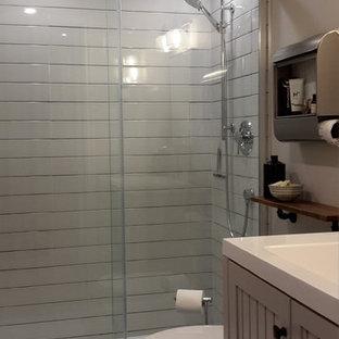 Ispirazione per una piccola stanza da bagno con doccia industriale con ante in stile shaker, ante grigie, WC monopezzo, piastrelle grigie, piastrelle in ceramica, pareti grigie, pavimento in mattoni e top in superficie solida
