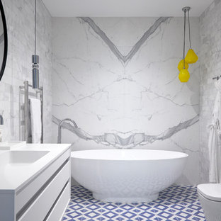 Design ideas for a medium sized contemporary ensuite bathroom in London with flat-panel cabinets, white cabinets, a freestanding bath, a corner shower, a one-piece toilet, grey tiles, porcelain tiles, ceramic flooring, a built-in sink, granite worktops, blue floors and a hinged door.