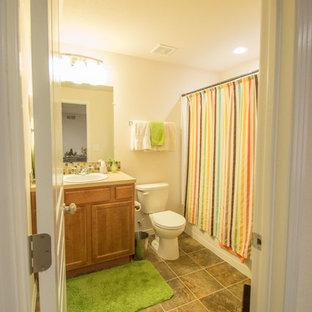 Ispirazione per una piccola stanza da bagno per bambini tradizionale con ante con bugna sagomata, ante in legno scuro, vasca ad alcova, vasca/doccia, WC a due pezzi, pareti beige, pavimento in linoleum, lavabo da incasso e top in laminato