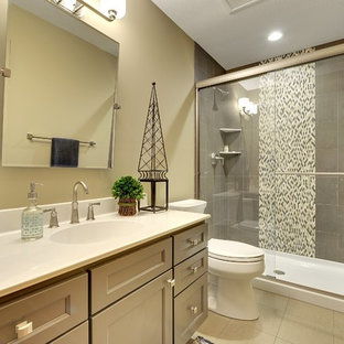 Bathroom - small transitional 3/4 gray tile and porcelain tile ceramic tile and beige floor bathroom idea in Minneapolis with gray cabinets, beige walls, solid surface countertops, a two-piece toilet, an integrated sink and recessed-panel cabinets