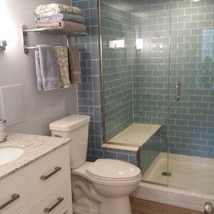 Idéer för små funkis bastur, med släta luckor, vita skåp, en dusch i en alkov, en toalettstol med separat cisternkåpa, blå kakel, glaskakel, blå väggar, klinkergolv i porslin, ett undermonterad handfat och granitbänkskiva