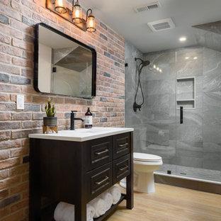 Diseño de cuarto de baño con ducha, industrial, de tamaño medio, con armarios tipo mueble, puertas de armario negras, ducha empotrada, sanitario de dos piezas, baldosas y/o azulejos grises, baldosas y/o azulejos de porcelana, suelo vinílico, lavabo bajoencimera, encimera de cuarzo compacto, suelo beige, ducha con puerta con bisagras, encimeras blancas y paredes blancas