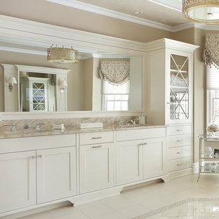 Modelo de cuarto de baño principal, clásico, grande, con armarios con paneles empotrados, puertas de armario blancas, bañera exenta, paredes beige, suelo de piedra caliza, lavabo bajoencimera, encimera de granito y suelo blanco