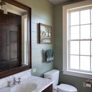 Idée de décoration pour une salle de bain chalet avec un lavabo encastré, un placard avec porte à panneau surélevé, des portes de placard en bois sombre et un mur vert.