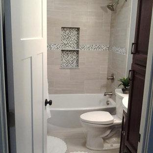 Esempio di una piccola stanza da bagno con doccia classica con ante con bugna sagomata, ante in legno bruno, vasca ad alcova, vasca/doccia, WC a due pezzi, piastrelle beige, piastrelle grigie, piastrelle bianche, piastrelle in ceramica, pareti beige, pavimento con piastrelle in ceramica, lavabo a colonna e top in superficie solida