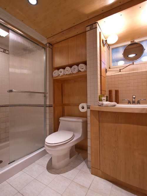 cabinets over toilet in bathroom. small trendy 3/4 beige tile and ceramic floor alcove shower photo in cabinets over toilet bathroom