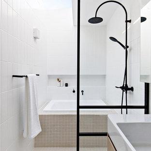 На фото: маленькая главная ванная комната в современном стиле с светлыми деревянными фасадами, японской ванной, душевой комнатой, белой плиткой, керамической плиткой, белыми стенами, подвесной раковиной, бежевым полом и открытым душем с