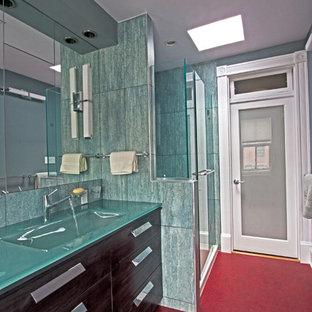 Diseño de cuarto de baño actual con lavabo integrado, puertas de armario grises, encimera de vidrio, baldosas y/o azulejos verdes, baldosas y/o azulejos de porcelana, armarios con paneles lisos, ducha empotrada y sanitario de una pieza
