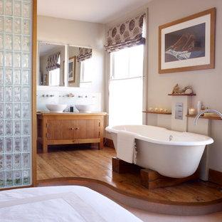 Modelo de cuarto de baño principal, contemporáneo, de tamaño medio, con lavabo sobreencimera, armarios con paneles lisos, puertas de armario de madera oscura, bañera exenta, paredes beige y suelo de madera en tonos medios