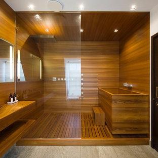 Foto de cuarto de baño principal, contemporáneo, con armarios abiertos, puertas de armario de madera oscura, bañera japonesa, ducha empotrada, paredes marrones, suelo de cemento, lavabo integrado, encimera de madera, ducha abierta y encimeras marrones