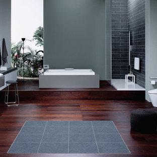Immagine di una grande stanza da bagno padronale moderna con ante lisce, ante grigie, vasca da incasso, doccia aperta, lavabo a bacinella, WC monopezzo, piastrelle in ceramica, pareti grigie, parquet scuro, top in superficie solida, pavimento marrone e doccia aperta