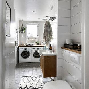 Modelo de cuarto de baño con ducha, contemporáneo, sin sin inodoro, con armarios con paneles empotrados, puertas de armario de madera oscura, sanitario de pared, baldosas y/o azulejos blancos, paredes blancas, lavabo integrado, suelo gris y ducha abierta