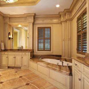 Modelo de cuarto de baño principal, tradicional, grande, con armarios con paneles con relieve, puertas de armario beige, bañera esquinera, sanitario de una pieza, paredes beige, suelo de piedra caliza, lavabo bajoencimera, encimera de ónix y suelo beige