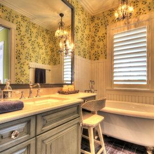На фото: с высоким бюджетом главные ванные комнаты среднего размера в стиле кантри с фасадами с выступающей филенкой, серыми фасадами, ванной на ножках, желтыми стенами, темным паркетным полом, врезной раковиной, столешницей терраццо и коричневым полом