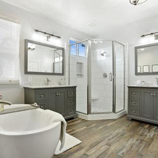 Réalisation d'une salle de bain principale design avec des portes de placard grises, une baignoire indépendante, une douche d'angle, un mur gris, sol en stratifié, un lavabo encastré, un plan de toilette en marbre, un sol marron, une cabine de douche à porte battante, un plan de toilette gris, meuble simple vasque et meuble-lavabo sur pied.