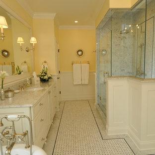 Esempio di una stanza da bagno chic di medie dimensioni con lavabo sottopiano, consolle stile comò, ante bianche, top in marmo, vasca con piedi a zampa di leone, piastrelle bianche, piastrelle in pietra, pareti gialle e pavimento in marmo