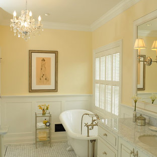 Claw-foot bathtub - mid-sized traditional white tile and stone tile marble floor claw-foot bathtub idea in San Francisco with an undermount sink, raised-panel cabinets, white cabinets, marble countertops, a two-piece toilet and yellow walls